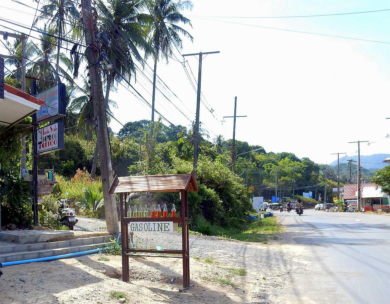 Thailand | Hauptstraße Richtung Süden auf Ko Lanta. Eine Tankstelle im Vordergrund, Häuser und Shops am Rand einer geteerten Straße