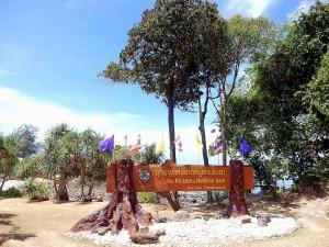Thailand | Mu Ko Lanta National Park. Ein braunes Holzschild mit der Aufschrift Mu Ko Lanta National Park Krabi Thailand im Vordergrund, das Meer, Baume und Palmen im Hintergrund