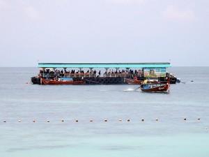 Thailand | Bootanleger auf Ko Lipe inmitten im Meer mit abreisenden Touristen die auf die Fähre zum Festland warten