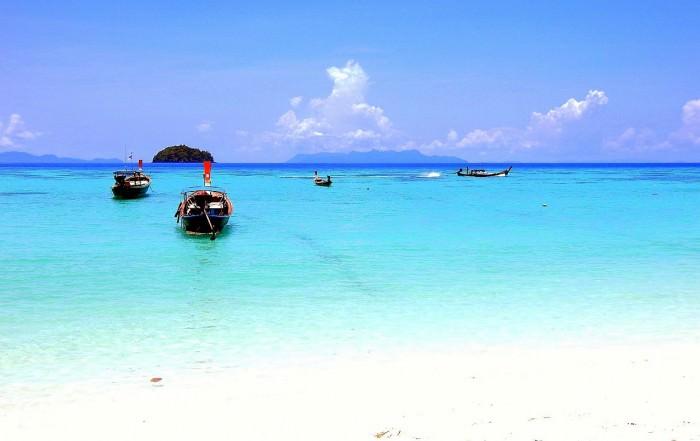 Thailand | Sunrise Beach auf Ko Lipe. Türkisfarbenes Wasser, weißer Sandstrand, blauer Himmel, ein paar Boote im Wasser