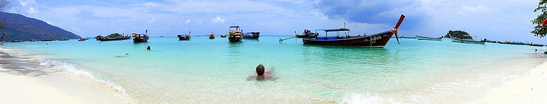 Thailand | Sunrise Beach auf Ko Lipe. Panorama des weißen Strandes , mit türkisfarbenem Wasser , ein paar Booten und Henning beim Baden mit dunklen Gewitterwolken am Himmel