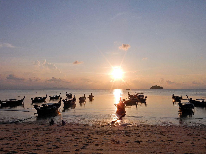 Thailand | Sonnenaufgang am Sunrise Beach auf Ko Lipe. Blick auf das Wasser mit einigen Booten und den Horizont an dem gelblich die Sonne aufgeht