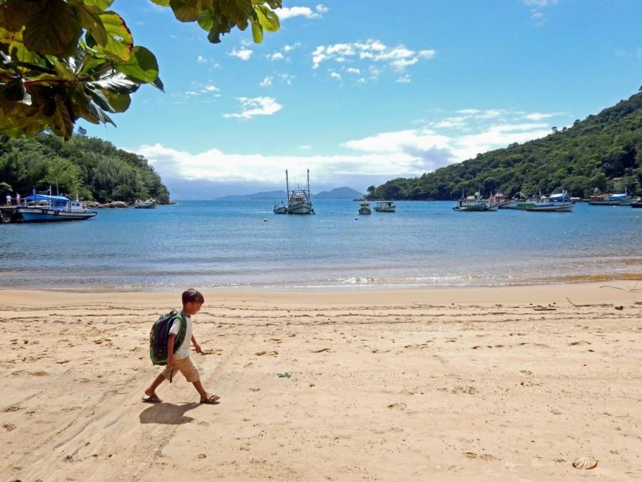Brasilien | Ilha Grande, Der vermutlich coolste Schulweg der Welt, mit einem kleinen Jungen der am Strand entlang vom Unterricht zurückkehrt