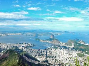 Brasilien | Rio de Janeiro, Der Blick vom Corcovado liefert bei Sonnenschein eine atemberaubende Kulisse mit der Stadt im Vordergrund vorm dem Meer mit dem emporragenden Zuckerhut