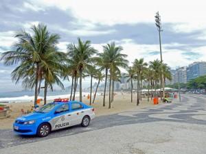 Rio de Janeiro | Sicherheit: blau-weißer Polizeiwagen vor den Palmen der Copacabana