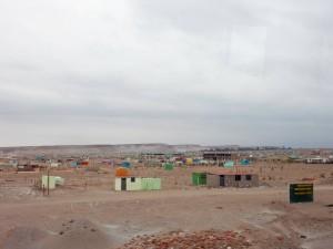 Peru | Ein Dorf mitten in den Anden auf dem Weg von Arequipa nach Cusco. Blick auf kleine viereckige Häuser aus Stein in bunten Farben mitten in einer Wüstenlandschaft