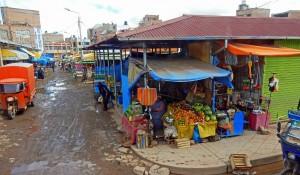 Peru | Nebenstraße von Deustua auf der Fahrt mit dem Bus von Arequipa nach Cusco. Blick auf einen kleinen Straßenhändler mit Obst, Blechhäuser, und Wasserpfützen auf dem Lehmboden