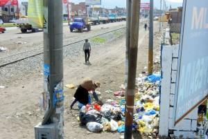 Peru | Die Hauptstraße von Juliaca. Eine Frau wühlt in Müllbergen am Straßenrand