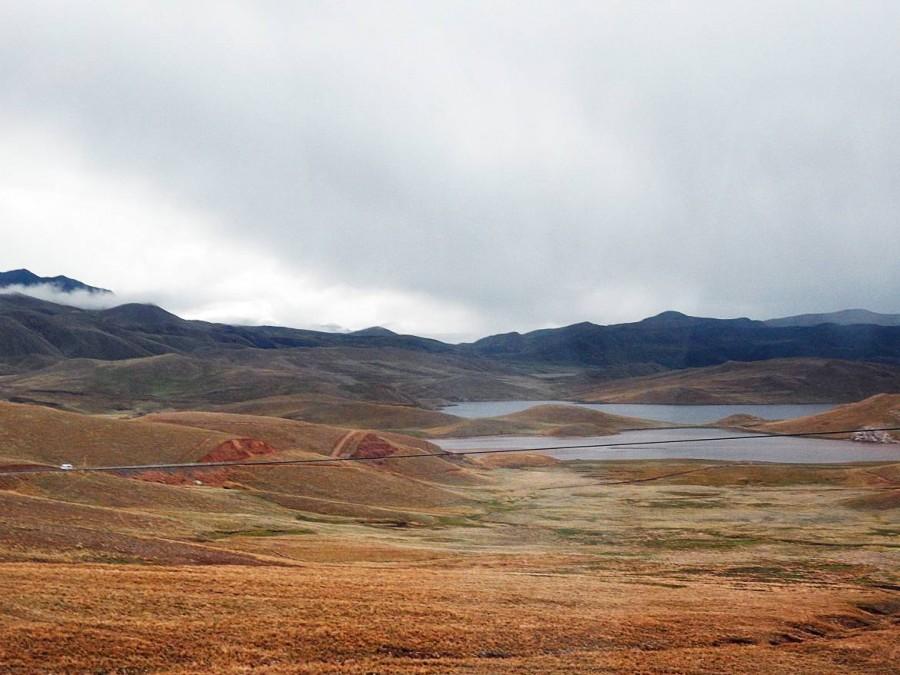 Peru | Auf dem Weg mit dem Bus von Arequipa nach Cusco geht es durch das Salinas Aguada Blanca National Reserve. Panorama aus dem Busfenster auf bunte Hügel und einen kleinen See