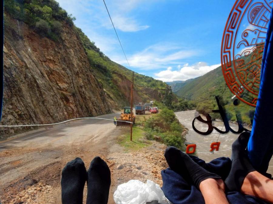 Busfahren | Peru: Premiumplätze mit Panorama-Aussicht auf der Fahrt mit Bus von Cusco über Abancay nach Ica. Blick auf die Straße, ein Fluss der entlang führt, blauen Himmel, umgeben von sattgrünen Berghängen und unsere Füße in schwarzen Socken
