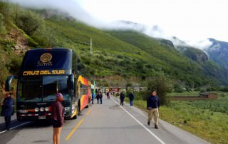 Busfahren | Peru: Auf der Fahrt mit dem Bus von Cusco über Abancay nach Ica standen wir 12 Stunden in einer Straßensperrung wegen eines Erdrutsches . Blick auf die Busschlange inmitten grüner Berge unser Cruz del Sur Bus ganz vorne