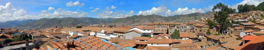 Peru | Panorama über den Dächern von Cusco. Blick über die Stadt mit grünen Bergen im Hintergrund bei blauem HImmel