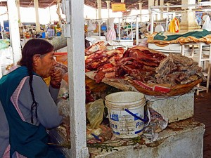 Peru | Lecker Fleisch auf dem Markt El Marcado San Pedro in Cuzco. Eine Frau sitzt hinter Fleischbergen in der Markthalle