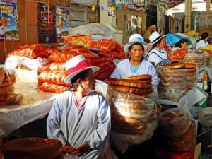 Peru | Brot-Verkauf am Markt El Mercado San Pedro in Cuzco. Blick auf einige Frauen, die vor rießen Laiben mit Brot sitzen und Hüte tragen