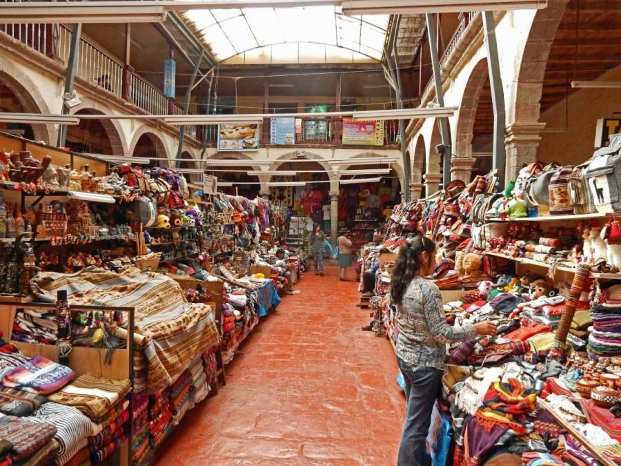 Peru | Souvenirs aus Alpaca Wolle gibt es überall in Cusco. Blick in eine Markthalle mit zahlreichen Verkaufsständen von Pullovern, Taschen, Hüten, etc.