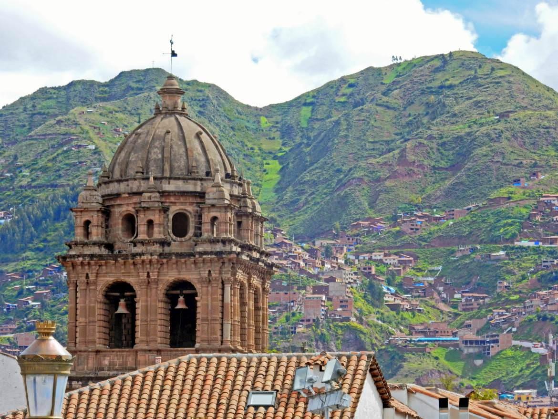 Peru | Kathedrale von Cusco am Plaza de Armas mit Blick auf sattgrüne Berge die die Stadt umgeben
