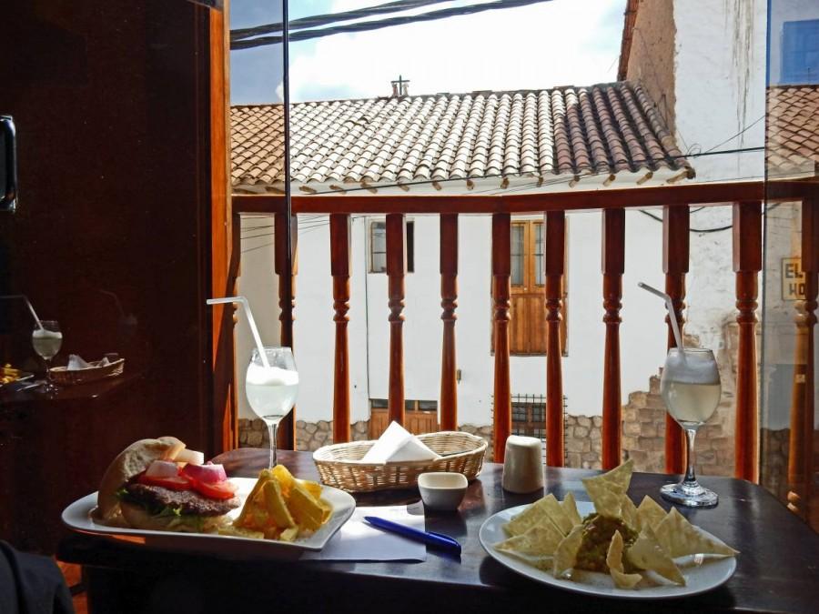 Peru | Pisco Sour, Alpaca Burger und Nachos con Guacamole im Restaurant Blue Alpaca in Cusco. Blick über den Tisch mit den Gerichten aus dem geöffneten Fenster in einer Gasse in Cusco