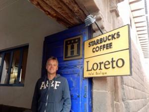 Peru | Starbucks in Cusco am Plaza de Armas mit exzellentem Free Wifi. Henning steht vor dem Schild zum Eingang des Coffe-Shops