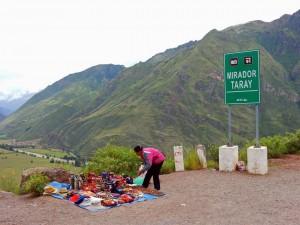 Peru | Heiliges Tal, 2. Stopp der Tour: Panoramaaussicht ins Sacred Valley am Mirador Taray . Eine Frau breitet gerade ihre Souvenirs auf dem Boden aus für anhaltende Touristenbusse