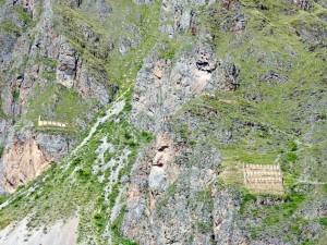 Peru | Heiliges Tal, Ollantaytambo Ruinen, Gesicht des Sonnengott der Inka im Stein und Vorratskammern der Inka. Blick auf ein in Stein gehauenes Gesicht und Höhlen im Berg, die als Vorratskammer für Lebensmittel genutzt wurden