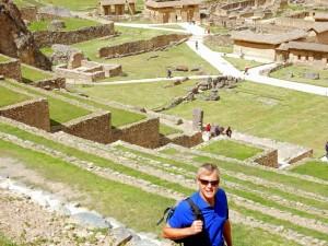 Peru | Heiliges Tal, Ollantaytambo Ruinen, Zahlreiche Treppen wirst Du beim Rundgang durch die Inka-Ruine zurücklegen. Henning im Vordergrund mit dem Blick nach unten über die Terrassen hinweg