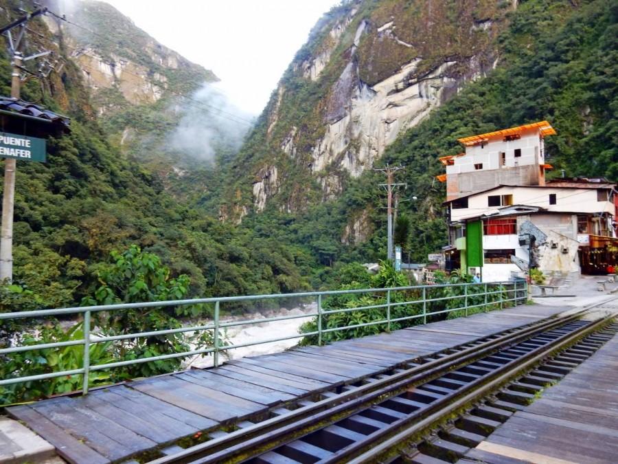 Peru | Machu Picchu, Gegenüber der Brücke fährt der Bus von Aguas Calientes zum Eingang Machu Picchu ab. Blick auf eine Brücke mit Zuggleisen inmitten der Berge