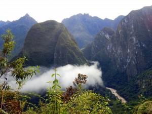 Peru | Machu Picchu, Panorama vom Trail beim Aufstieg von Aguas Calientes zum Weltwunder vor Sonnenaufgang. Blick auf das in Wolken verhüllte Urubamba Tal