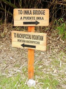 Peru | Machu Picchu Montana, Wegweiser zum Berg und zur Inka Brücke als Schilder aus Holz in der Inka-Ruine