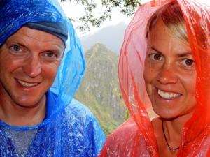 Peru | Machu Picchu, schnell kann´s auch mal regnen in der Inka-Stadt. Karin und Henning mit ihrem Regenschutz einem roten und blauen Poncho bei Regen in der Inka-Ruine