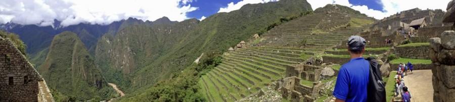 Peru | Machu Picchu, Panorama auf die meterhohen Terrassen in der Inka-Ruine. Henning im Vordergrund, sattgrüne mit Gras bewachsenen Terrassen umgeben von hohen Bergen des Urubamba Tal im Hintergrund