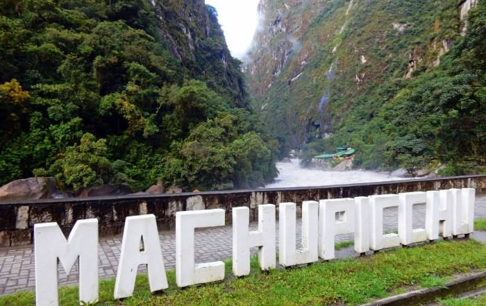 Peru | Machu Picchu, Inka-Stadt und Weltwunder. Blick auf die weißen Buchstaben Machu Picchu vor dem Fluss und grünen Bergen im Urubamba Tal