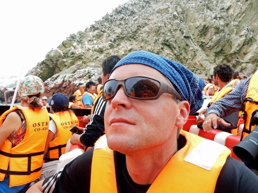 Paracas Nationalpark | Islas Ballestas Tour, Wir und andere Touristen auf dem Boot beim Bestaunen der Tierwelt. Henning in Nahaufnahme mit Sonnenbrille und orangefarbener Schwimmweste