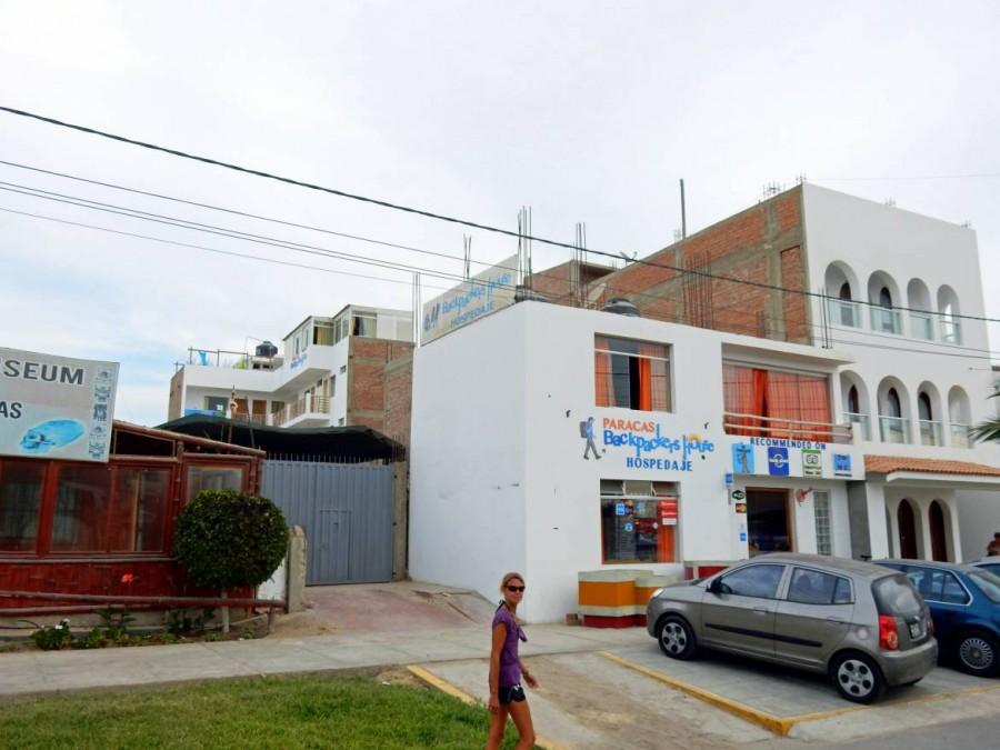 Peru | Backpackers House, unsere Unterkunft in Paracas. Blick auf das von außen hässliche Hostel mit Karin im Vordergrund