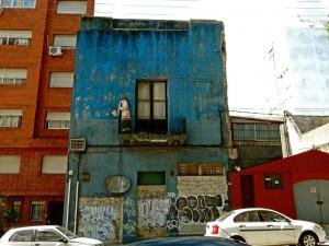 Uruguay | Montevideo, Heruntergekommene Fassaden der Altstadt kunstvoll in Szene gesetzt am Beispiel eines blauen alten Hausen mit musizierender Skulptur auf dem brüchigen Balkon