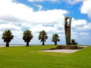 Uruguay | Montevideo, Zahlreiche Monumente und Denkmäler finden sich entlang des Rambla wie hier vor schönen Palmen im Wind