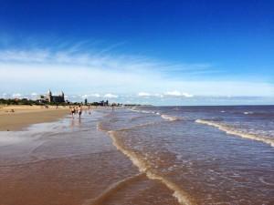 Uruguay | Montevideo, Je weiter man dem Rambla folgt, desto ruhiger werden die Strände, wie hier in Carrasco etwa 17 km von der Altstadt entfernt. Breiter ruhiger Strand, braunes Meerwasser vor blauem Himmel