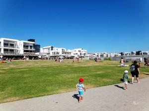 Südafrika | Kapstadt, Unterkünfte und Restaurants am Blouberg Beach. Blick auf die Promenade mit einigen Touris