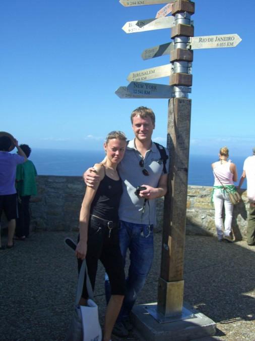 Südafrika | Kapstadt, Kap-Halbinsel, Cape Point am Leuchtturm. Karin und Henning vor einem Pfahl mit Wegweisern Richtung verschiedener Städte