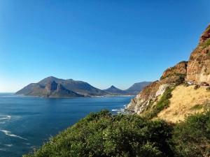 Südafrika | Kapstadt, Kap-Halbinsel, Panorama Richtung Hout Bay vom Chapmans Peak Drive und in die Bucht entlang der Küstenstraße bei blauem Himmel