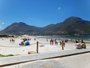 Südafrika | Kapstadt, Kap-Halbinsel, Strand von Hout Bay. Blick auf die Bucht mit einigen Badegästen, die Bergketten im Hintergrund bei blauem Himmel