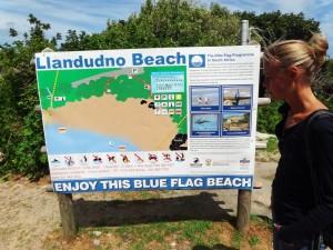 Südafrika | Kapstadt, Kap-Halbinsel, Llandudno Beach Wegweiser zum Strand mit Karin im Vordergrund. Einer unserer Tipps & Highlight. Hier gibt es viele interessante Orte