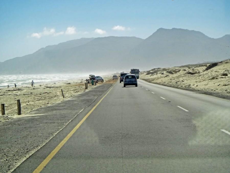 Südafrika | Kapstadt, Kap-Halbinsel, Strand von Muizenberg. Blick auf die Straße entlang des Strandes mit Bergkette im Hintergrund