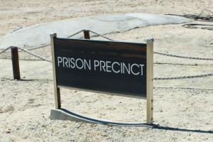 Südafrika | Kapstadt, Robben Island Tour, Gefängnis Bezirk. Blick auf ein braunes Schild mit der englischen Aufschrift Prison Precinct