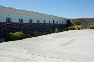 Südafrika | Kapstadt, Tour nach Robben Island, Innenhof des Gefängnis in dem Nelson Mandela in Haft war. Blick auf den steinigen Hof und hohe Gefängnismauern