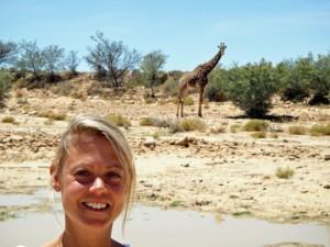 Südafrika | Auf der Suche nach den BIG 5 im Inverdoorn Game Reserve bei Kapstadt. Karin im Vordergrund der Steppenlandschaft mit einer Giraffe im Hintergrund