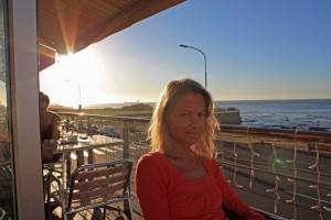 Südafrika | Kapstadt, Sundowner in einer Bar im Stadtteil Sea Point. Karin sitzt auf dem Balkon der Bar mit dem Meer und der untergehenden Sonne im Hintergrund
