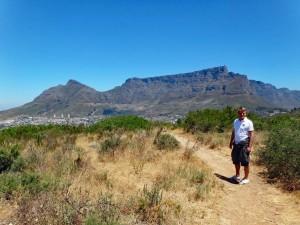 Südafrika | Kapstadt, Wanderweg auf dem Signal Hill mit Blick auf den Tafelberg . Henning im Vordergrund umgeben von Gebüsch, Teile der Stadt und der Tafelberg im Hintergrund bei blauem Himmel
