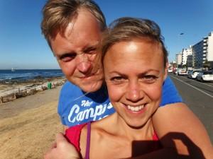 Südafrika | Kapstadt, Spaziergang entlang der Strandpromenade von Sea Point über Greenpoint bis zur V&A Waterfront. Karin und Henning als Selfie in Nahaufnahme, die Straße und das Meer im Hintergrund