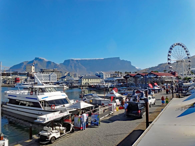Südafrika | Kapstadt, Panorama in der V&A Waterfront mit dem Tafelberg im Hintergrund. Boote, Restaurants, Shops, Touristen bei blauem Himmel