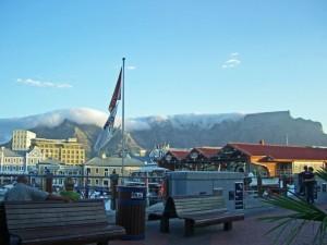 Südafrika | Kapstadt, V&A Waterfront mit Blick auf den Tafelberg samt Tischtuch bei blauem Himmel im Vordergrund ein Paar auf einer Bank von hinten fotografiert